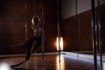 Pole dancer practicing pole dance in dark studio — Stock Photo