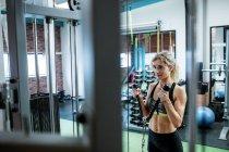 Mulher realizando exercício de alongamento no ginásio — Fotografia de Stock