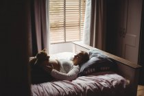 Femme enceinte tenant un ours en peluche sur le ventre tout en dormant dans la chambre à coucher à la maison — Photo de stock