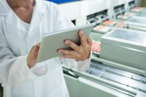 Midsection of female staff using digital tablet next to production line in egg factory — Stock Photo