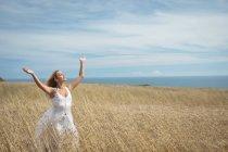 Mulher loira despreocupada em pé no campo com os braços levantados — Fotografia de Stock