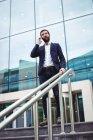 Бизнесмен разговаривает по мобильному телефону у входа в офисное здание — стоковое фото