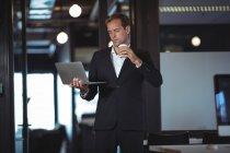 Affari che prendono il caffè mentre usano il computer portatile in ufficio — Foto stock
