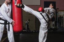 Вид сбоку спортсменки и спортсмена, практикующего карате с боксерской грушей в студии — стоковое фото