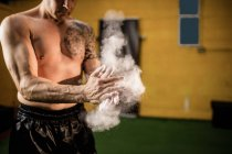 Cropped image of boxer applying talcum powder on hands in gym — Stock Photo