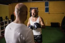 Selective focus of two thai boxers practicing boxing in gym — Stock Photo