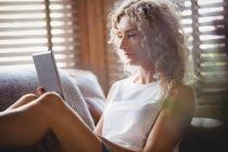 Женщина пользуется цифровым планшетом в гостиной дома — стоковое фото