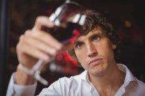 Barman regardant un verre de vin rouge au comptoir du bar — Photo de stock