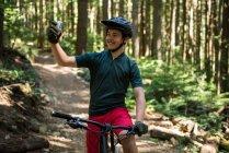 Мужчина-велосипедист делает селфи на мобильном телефоне в лесу — стоковое фото