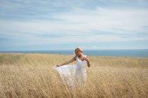 Беззаботная блондинка в белом платье стоит в поле — стоковое фото