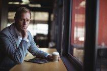 Портрет бизнесмена, сидящего в кафе с цифровым планшетом и кофе — стоковое фото