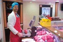 Портрет м'ясника перевірка ваги м'яса на лічильник в магазин м'яса — стокове фото