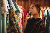 Учасник чемпіонату з мобільного телефону під час вибору одягу на вішалки в магазині одягу — стокове фото