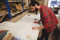 Человек смотрит на чертеж в интерьере лодочной станции — стоковое фото