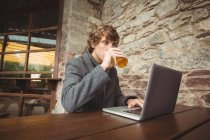 Mid section of man holding glass of beer and using laptop at bar — Stock Photo
