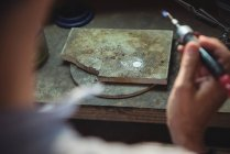 Крупный план ремесленницы с помощью паяльника в мастерской — стоковое фото