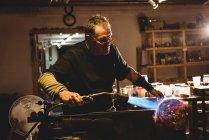 Стеклодув выдувает пропановый газ на готовый кусок стекла на стекольном заводе — стоковое фото