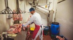 Açougueiro pendurado carne vermelha na sala de armazenamento no açougue — Fotografia de Stock
