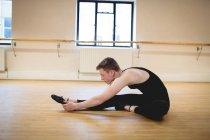 Вид сбоку Балерино, выполняющего упражнения на растяжку на полу в студии — стоковое фото