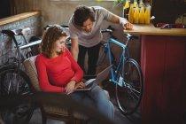 Couple utilisant un ordinateur portable dans un magasin de vélos — Photo de stock