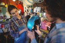 Mechanics examining a bicycle helmet in bicycle workshop — Stock Photo