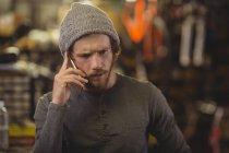 Механік говорити на мобільний телефон у магазин велосипедів — стокове фото