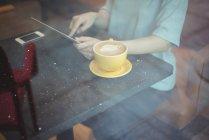 Mulher usando tablet digital enquanto toma café no café — Fotografia de Stock