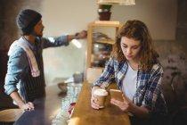 Механік за допомогою мобільного телефону під час за кавою в лічильника в майстерні — стокове фото
