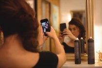 Mujer tomando selfie desde el teléfono móvil en el salón - foto de stock