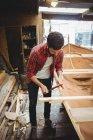 Uomo preparazione cornice barca in legno in cantiere — Foto stock