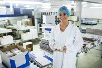 Portrait du personnel féminin tenant un carton d'œufs dans une usine — Photo de stock