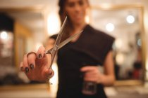 Female hairdresser holding scissors at saloon — Stock Photo