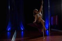 Bailarina de poste practicando pole dance en estudio oscuro - foto de stock