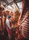 Açougueiro examinando a carne vermelha pendurada na sala de armazenamento no açougue — Fotografia de Stock