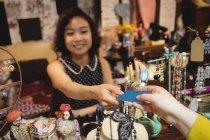 Client donnant sa carte de crédit à la caissière au comptoir de facturation — Photo de stock