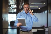 Бізнесмен, дивлячись на цифровий планшетний під час розмови по мобільному телефону в офісі — стокове фото