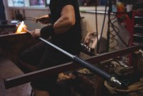 Cropped image of Glassblower shaping molten glass at glassblowing factory — Stock Photo