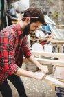 Людина, використовуючи ручний інструмент гладкою і рівень поверхні Планк у верфі — стокове фото