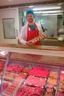 Портрет м'ясника стоїть на м'ясних лічильник м'ясників магазин, у — стокове фото