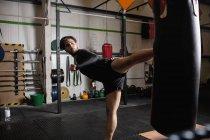 Вид сбоку мужской боксер практикующий бокс с боксерской грушей в фитнес-студии — стоковое фото