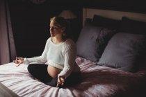 Беременная женщина, занимающаяся йогой в спальне дома — стоковое фото
