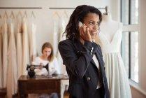 Designer de moda assumindo telefone celular no estúdio — Fotografia de Stock