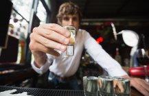 Портрет бармена, держащего рюмку текилы за барной стойкой в баре — стоковое фото
