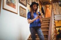 Персонал женского пола использует мобильный телефон на лестнице в бутик-магазине — стоковое фото