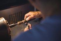 Руки ремесленницы, работающей на машине в мастерской — стоковое фото