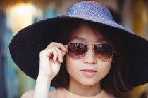 Retrato de mujer con gafas de sol en tienda boutique - foto de stock