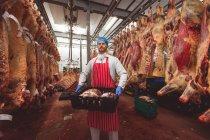 Açougueiro transportando caixa de carne vermelha na sala de armazenamento no açougue — Fotografia de Stock