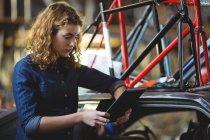Механик с помощью цифрового планшета во время ремонта велосипеда в мастерской — стоковое фото
