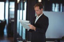 Uomo d'affari che legge una relazione finanziaria in carica — Foto stock