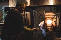 Обдув стеклодувом выдувной кусок стекла с мокрой тканью на стеклодувном заводе — стоковое фото